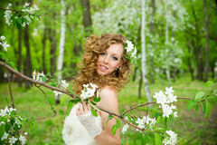 Beautiful bride in a white dress in blooming gardens in the spring Stock Photo
