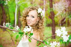 Beautiful bride in a white dress in blooming gardens in the spring Royalty Free Stock Photography