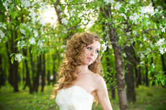 Beautiful bride in a white dress in blooming gardens Royalty Free Stock Photo