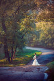 A beautiful bride in a white dress with a bouquet of flowers. In the Park Royalty Free Stock Images