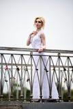 Beautiful bride in white dress on bridge Royalty Free Stock Photography