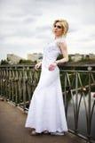 Beautiful bride in white dress on bridge Stock Photo