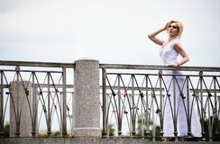 Beautiful bride in white dress on bridge Stock Image