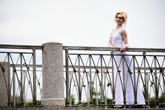Beautiful bride in white dress on bridge Royalty Free Stock Images