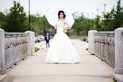 Beautiful bride in white dress on bridge witch umbrella.  royalty free stock photo