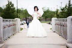 Beautiful bride in white dress on bridge witch umbrella Royalty Free Stock Photo