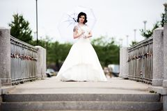 Beautiful bride in white dress on bridge witch umbrella.  royalty free stock photos