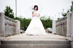 Beautiful bride in white dress on bridge witch umbrella Royalty Free Stock Photos