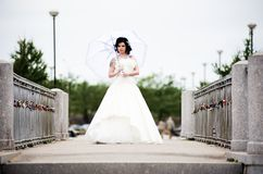 Beautiful bride in white dress on bridge witch umbrella Stock Photo