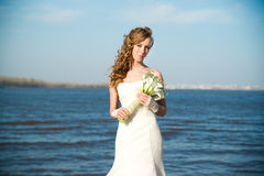 Beautiful bride in a white dress on coast of river Stock Image