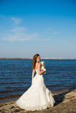 Beautiful bride in a white dress on coast of river Royalty Free Stock Photos