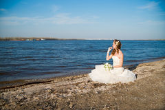 Beautiful bride in a white dress on coast of river Stock Images
