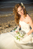 Beautiful bride in a white dress on coast of river Stock Photos