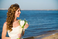 Beautiful bride in a white dress on coast of river Royalty Free Stock Photography