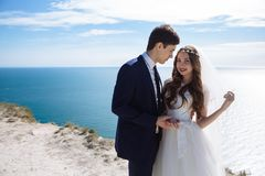 Beautiful bride in white dress and elegant groom in suit are standing and hugging on rock with ocean and blue sky on. Background stock image