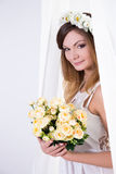 Beautiful bride in white dress with flowers standing near the wi. Young beautiful bride in white dress with flowers standing near the window Stock Photo