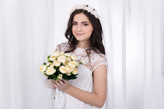 Beautiful bride in white dress with flowers. Standing near the window Royalty Free Stock Photography