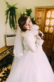 Beautiful bride in white dress and fur cape posing indoors Stock Photo