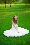 Beautiful bride in a white dress on green grass in summer Stock Images