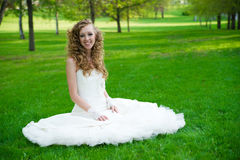 Beautiful bride in a white dress on green grass in summer Royalty Free Stock Photography