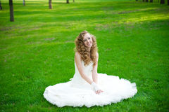 Beautiful bride in a white dress on green grass in summer Stock Photos