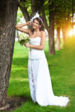 Beautiful bride in a white dress in a green park Royalty Free Stock Photos