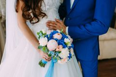 Bride in a white dress and groom in a blue tuxedo are standing next to the window and holding a wedding bouquet. Royalty Free Stock Images