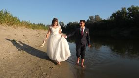 Beautiful bride in white dress and groom walk barefoot in water along edge of riverbank. loving couple goes hand in hand stock video footage