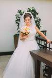 Beautiful bride in white dress standing near the baluster holding wedding bouquet of pale pink roses Stock Photos