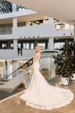 Beautiful bride in a white dress stands near the window at the hotel royalty free stock photos