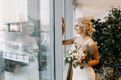 Beautiful bride in a white dress stands near the window in a hypermarket ,blonde stock image