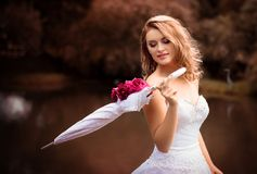 Beautiful bride in white dress with an umbrella, park royalty free stock image
