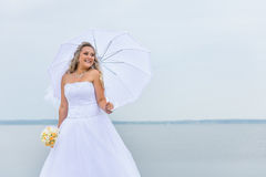 Beautiful bride in white dress with an umbrella. Beautiful bride in white dress with white umbrella and wedding bouquet of yellow and pink flowers, Lake Shore Royalty Free Stock Images