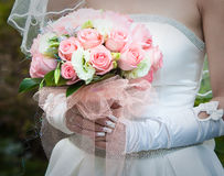 Beautiful bride in white gown holding bouquet Stock Photo