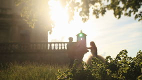 Beautiful bride in white gown holding hand of handsome groom near romantic vintage palace in warm sunset rays stock video footage