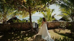 A beautiful bride in a white long wedding dress walks along a path among the palm trees to the groom. Solemn moment. The stock video