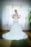 Beautiful bride in white wedding dress. Standing in her bedroom near the window Royalty Free Stock Images
