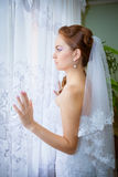 Beautiful bride in white wedding dress. Standing in her bedroom near the window Stock Image