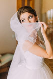 Beautiful bride in white wedding dress hiding her face behind the veil. Female portrait in bridal gown for marriage Stock Photos
