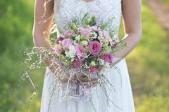 Beautiful bride in white wedding dress holding a bridal bouquet. Beautiful young bride in wedding dress and with a lovely mood in a spring forest royalty free stock photo