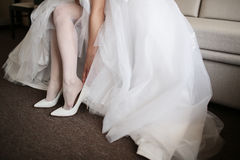 Beautiful bride in white wedding dress is holding shoes in her hands. . Close-up woman's arms. Stock Images