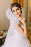 Beautiful bride in white wedding dress posing with veil. Female portrait in bridal gown for marriage Royalty Free Stock Photo