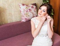Beautiful bride in white wedding dress puts on earring. Beauty model girl is wearing jewelry. Stock Photos