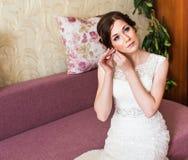 Beautiful bride in white wedding dress puts on earring. Beauty model girl is wearing jewelry. Stock Images