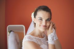 Beautiful bride in white wedding dress puts on earring Stock Photos