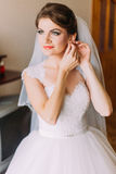 Beautiful bride in white wedding dress puts on earring. Female portrait in bridal gown for marriage. Cute lady indoors Stock Images