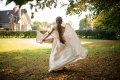 Beautiful bride in a white wedding dress running in the autumn park. Beautiful bride with a long hair in a white dress running in the green autumn park royalty free stock photos