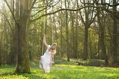 Beautiful bride in white wedding dress sitting on swing outdoors. Portrait of a beautiful bride in white wedding dress sitting on swing outdoors Stock Image