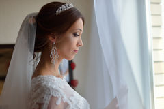 Beautiful bride in white wedding dress standing in her bedroom and looking in window, she waits for the groom. Royalty Free Stock Image