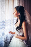 Beautiful bride in white wedding dress. Standing in her bedroom near the window Stock Photography